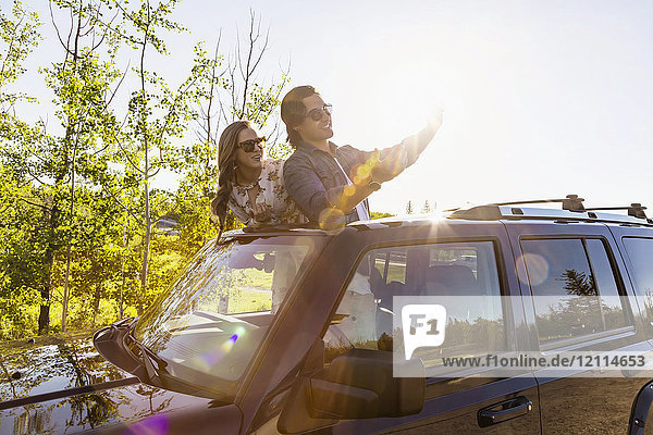 Young couple taking selfies with a cell phone in their vehicle; Edmonton  Alberta  Canada