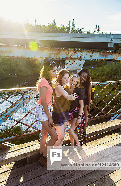 A group of four girlfriends pose for a self-portrait with a smart phone on a bridge in a park; Edmonton  Alberta  Canada