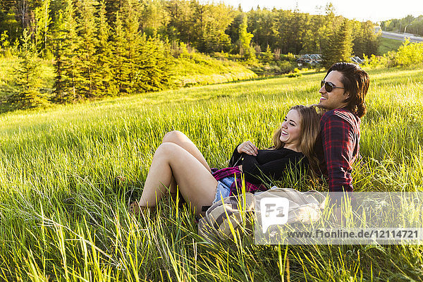 Young couple in a park sitting to rest during a hike in autumn; Edmonton  Alberta  Canada