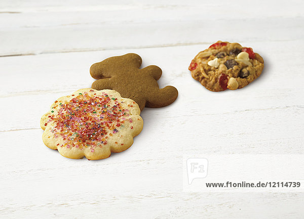 Variety of holiday cookies on a wooden white surface