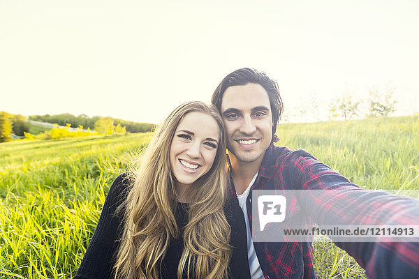 Young couple in a park posing for a self-portrait with their cell phone; Edmonton  Alberta  Canada