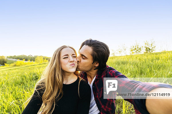 A young couple sits in a field taking a self-portrait while the young man kisses the young woman on the cheek; Edmonton  Alberta  Canada
