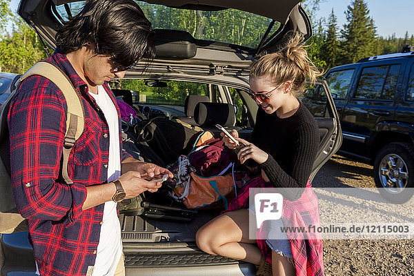 Young couple standing at the back of their packed vehicle with back door open and both using their smart phones; Edmonton  Alberta  Canada