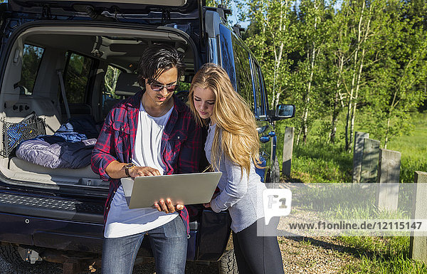 Young couple at their vehicle with the back open looking at a laptop computer; Edmonton  Alberta  Canada