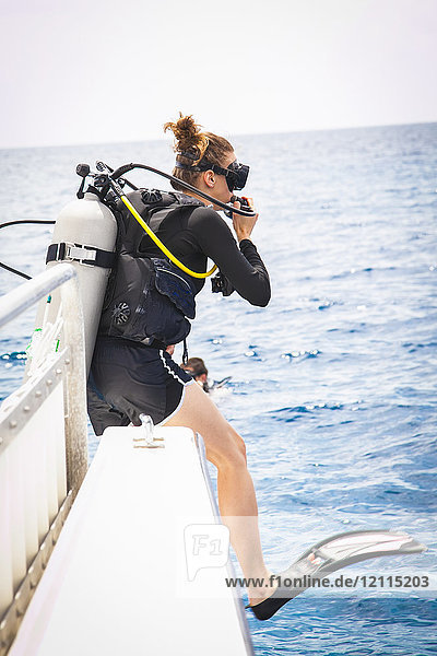 Female diver doing giant stride off dive boat; Negril  Jamaica