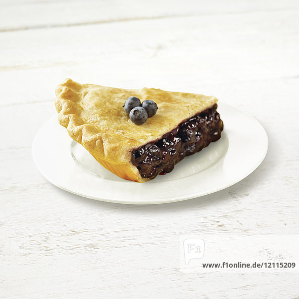 A piece of blueberry pie on a white plate with fresh blueberries garnishing the top