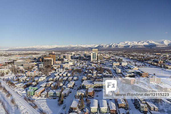 Aerial view of snow covering downtown Anchorage and the Chugach Mountains in the distance  the Park Strip and Capitan Cook Hotel visible in the foreground  South-central Alaska in winter; Anchorage  Alaska  United States of America