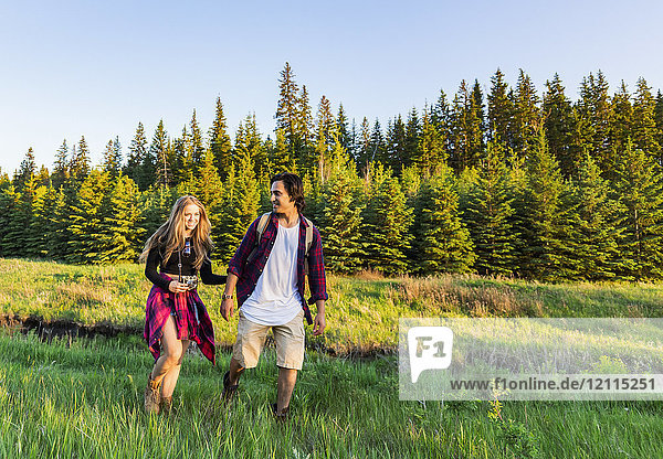 Young couple walking together on a hike in a city park in autumn; Edmonton  Alberta  Canada