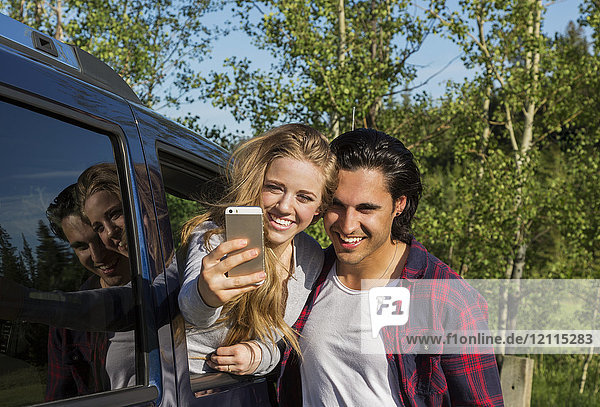 A young couple taking a self-portrait with their smart phone at their vehicle; Edmonton  Alberta  Canada