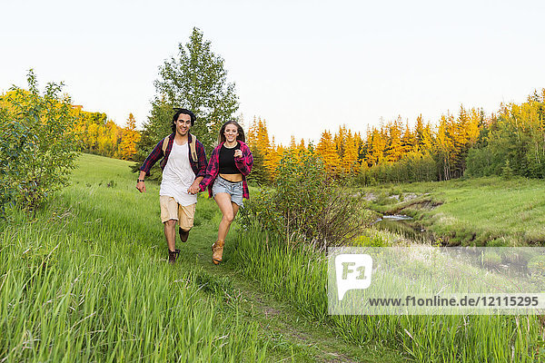 Young couple holding hands and running together down a trail in a city park; Edmonton  Alberta  Canada