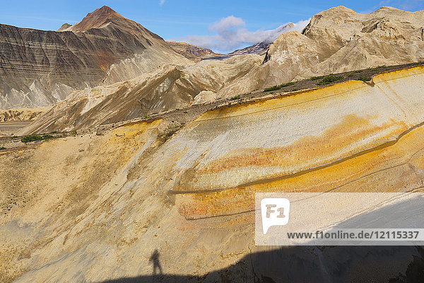 A photographer catches his shadow in a colorful canyon near the base of the ash-covered Knife Creek Glaciers in the Valley of Ten Thousand Smokes in Katmai National Park; Alaska  United States of America