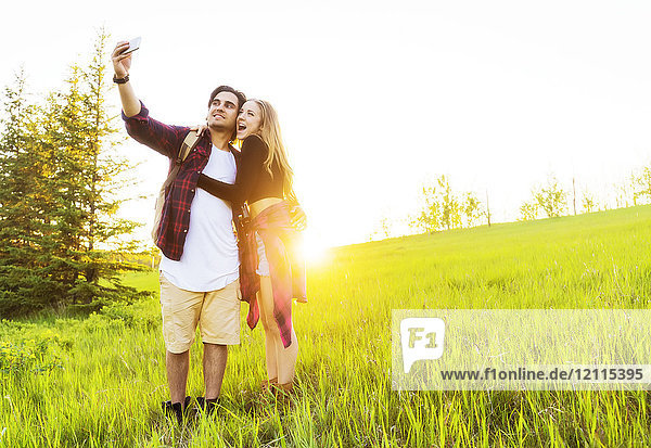 Young couple in a park posing for a self-portrait with their cell phone at sunset; Edmonton  Alberta  Canada