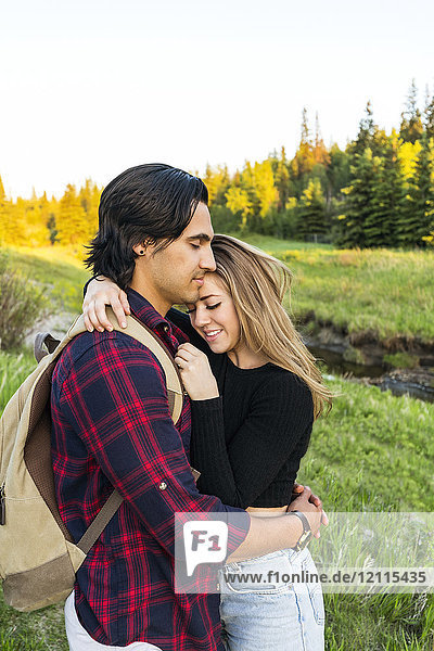 Young couple standing in a park in an embrace during a hike in autumn; Edmonton  Alberta  Canada