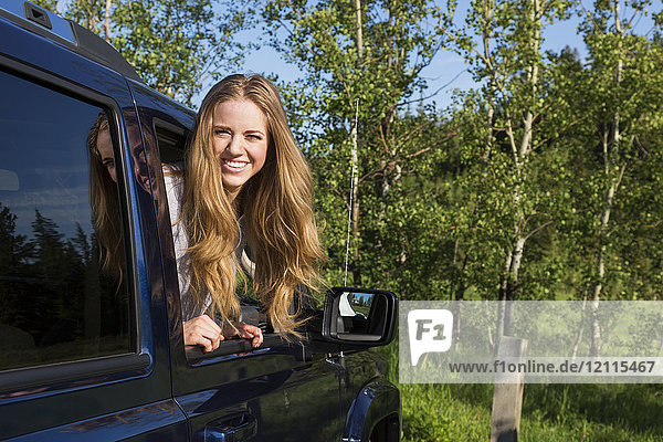 A beautiful young woman with long blond hair looking out a vehicle window and posing for the camera; Edmonton  Alberta  Canada