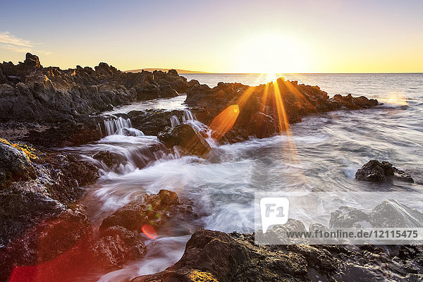 Dramatic sunset over the ocean with waterfalls along the rugged coastline; Wailea  Maui  Hawaii  United States of America