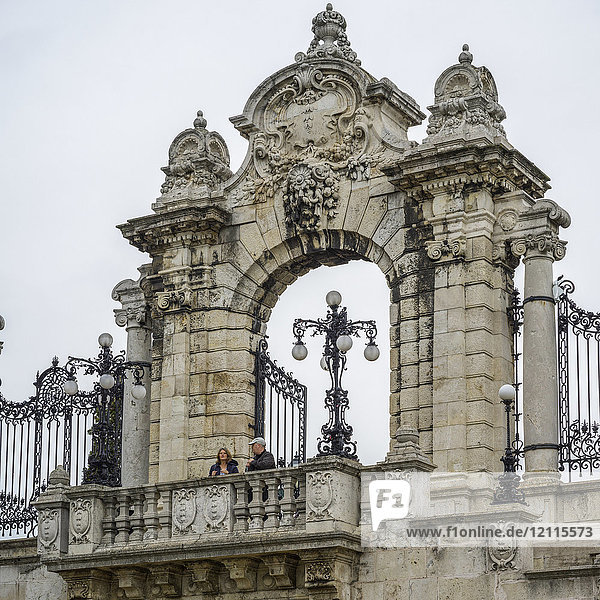 A couple stands on a balcony with an ornate archway behind them and decorative lamp posts; Budapest  Budapest  Hungary