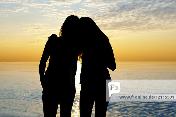 Silhouette of two teenage girls standing in an embrace looking out at a lake at sunset  Woodbine Beach; Toronto  Ontario  Canada