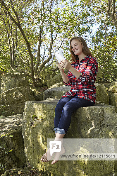 A teenage girl wearing jeans and a plaid shirt in bare feet sits on a boulder using her smart phone  Woodbine Beach; Toronto  Ontario  Canada