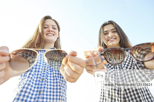 Two teenage girls posing and holding out their sunglasses towards the camera as if offering them to the viewer  Woodbine Beach; Toronto  Ontario  Canada