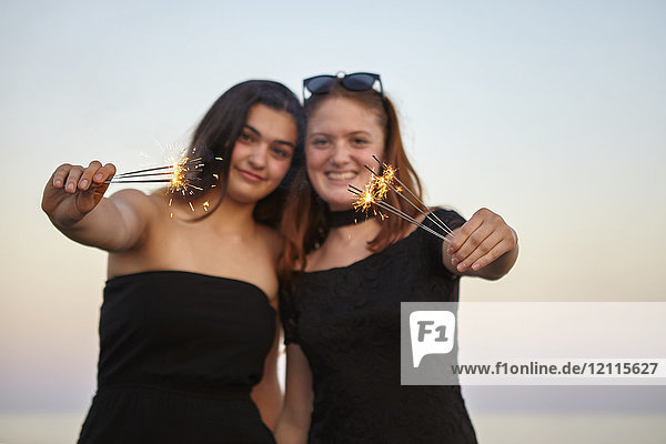 Two teenage girls in formal black dresses hold out sparklers towards the camera while outside at sunset  Woodbine Beach; Toronto  Ontario  Canada