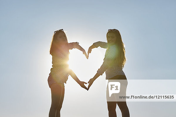 Two teenage girls stand making the shape of a heart with their arms as the sunlight shines through  Woodbine Beach; Toronto  Ontario  Canada