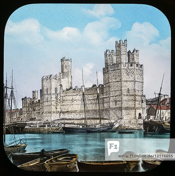 Magic Lantern slide circa 1900 hand coloured. created in 1887. Carnarvon caenarfon Castle  from the Ferry.—This view is taken from the other side of the River Seoint  and gives one a fair idea of the grandeur of this noble building  which is one of the finest ruins of its kind in the empire. The towers are of admirable proportions  that known as the Eagle Tower being the finest and strongest  and having three turrets above its roof  as seen in the view. From the summit of this tower we get a splendid prospect of surrounding scenery  and also a bird's-eye view of the Castle itself  and a notion of its stability  vastness  and venerability. This is another of the Castles erected by Edward I.