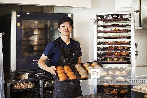 Mann  der in einer Bäckerei arbeitet  hält ein großes Tablett mit frisch gebackenen Brötchen in der Hand und lächelt in die Kamera.