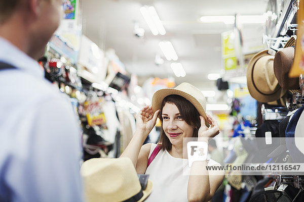 Smiling woman with brown hair stanching in a clothing store  trying on Panama hat.