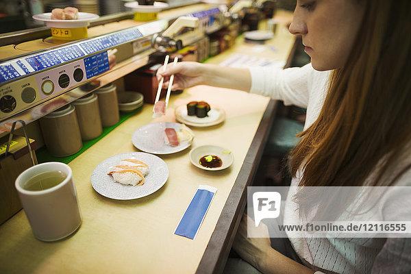 High angle view of woman eating in a sushi bar  with sushi train  Kaiten-zushi.