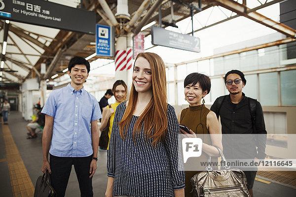 Kleine Gruppe von Menschen  die auf dem Bahnsteig einer U-Bahn-Station stehen  Tokio-Pendler.