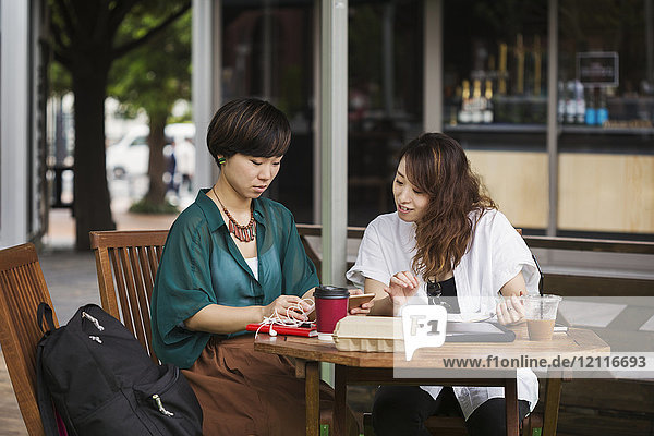 Two women with black hair wearing green and white shirt sitting at table in a street cafe  looking at digital tablet.