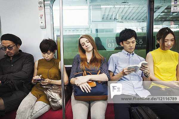 Five people sitting sidy by side on a subway train  Tokyo commuters.