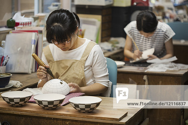 Woman working in a Japanese porcelain workshop  painting geometric pattern onto white bowls with paintbrush.