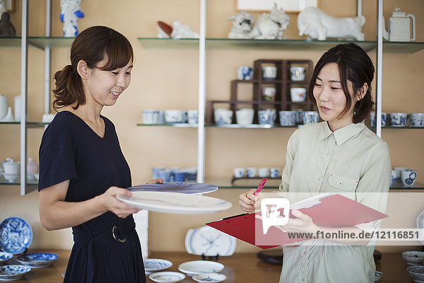 Two women standing in a Japanese porcelain shop  holding plates and document file.