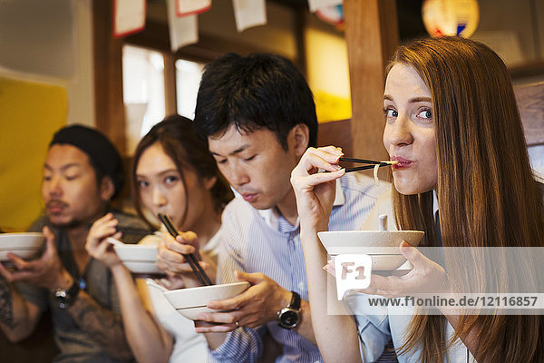Four people sitting sidy by side at a table in a restaurant  eating from bowls using chopsticks.