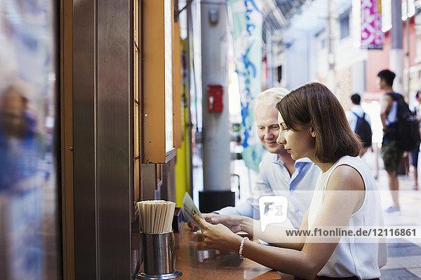 Junger Mann und Frau sitzen an einem Tisch in einem asiatischen Fast-Food-Restaurant und schauen sich die Speisekarte an.