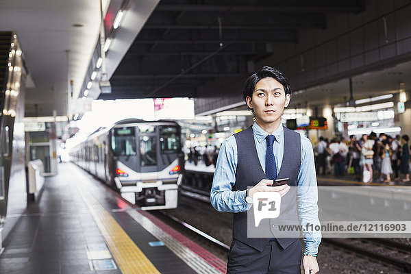 Businessman wearing blue shirt and vest standing on train station platform  holding mobile phone  looking at camera.