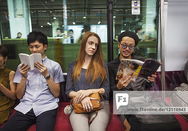 Three people sitting sidy by side on a subway train  reading Tokyo commuters.