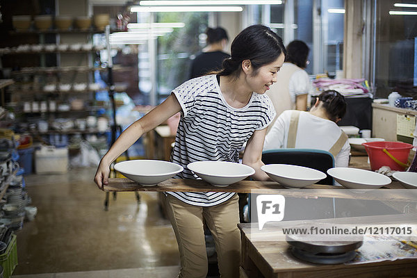 Woman standing in a Japanese porcelain workshop  holding long wooden tray with bowls.