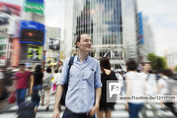 Ein junger kaukasischer Mann mit Rucksack auf einer belebten Straße in der Innenstadt von Tokio.