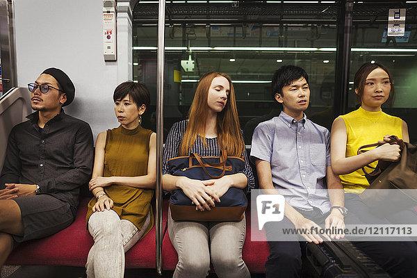 Fünf Menschen sitzen nebeneinander in einem U-Bahn-Zug  Tokio-Pendler.