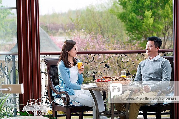 The middle-aged couple have their breakfast on the terrace
