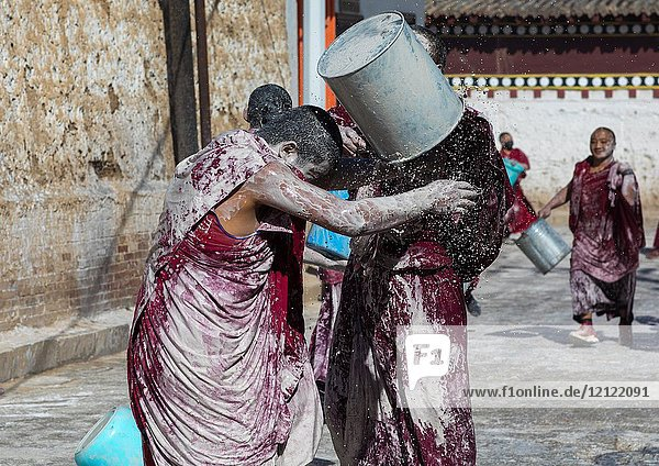 Tibetan monks enjoying a water fight after the yearly renovation of the Rongwo monastery  Tongren County  Longwu  China.