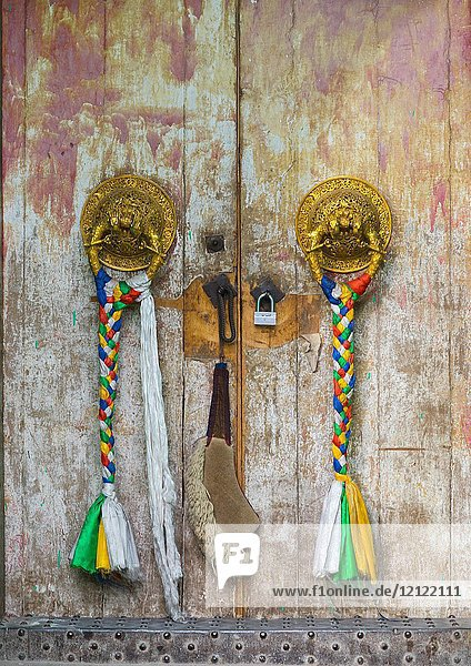 Ornate knockers on traditional buddhist door temple in Rongwo monastery  Tongren County  Longwu  China.