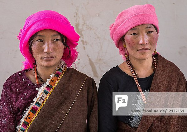 Portrait of tibetan nomads women with a pink headwears  Qinghai province  Tsekhog  China.