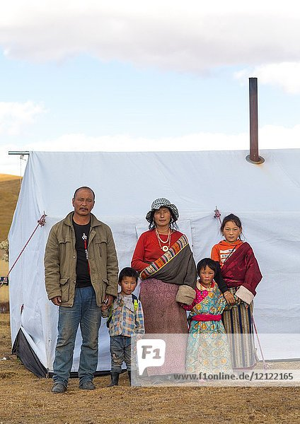 Portrait of a tibetan nomad family living in a tent in the grasslands  Qinghai province  Tsekhog  China.