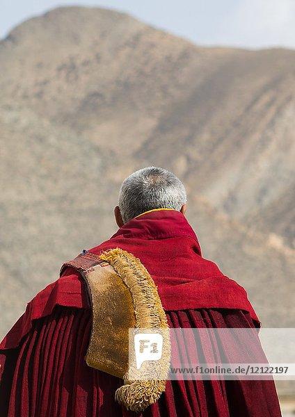 Tibetan monk wearing robe and yellow hat of the gelug order in Labrang monastery  Gansu province  Labrang  China.
