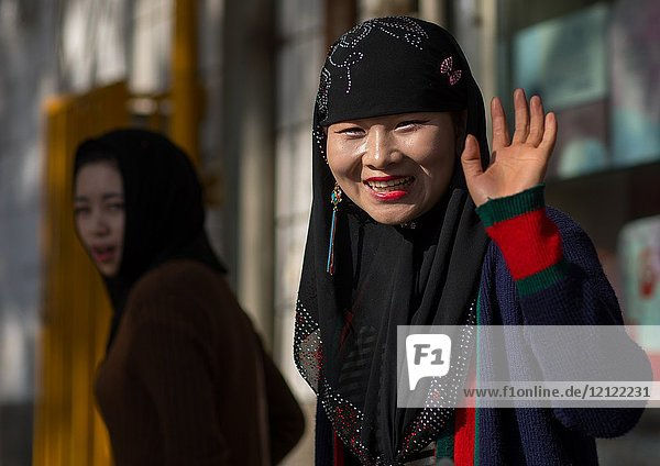 Hui muslim woman smiling in the street  Gansu province  Linxia  China.
