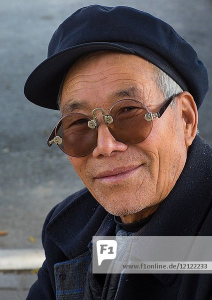 Old man with traditional sunglasses and cap  Gansu province  Linxia  China.