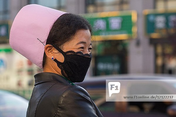Muslim woman with the traditional pink hat and a mask in the street  Gansu province  Linxia  China.